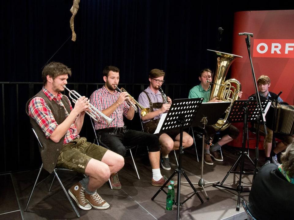 Fünf Blasmusikanten sitzen vor Notenständern und musizieren.