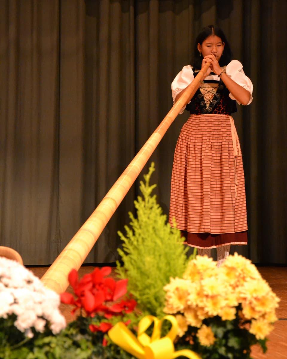 Die junge Alphornspielerin in einer Tracht während ihres Auftritts.