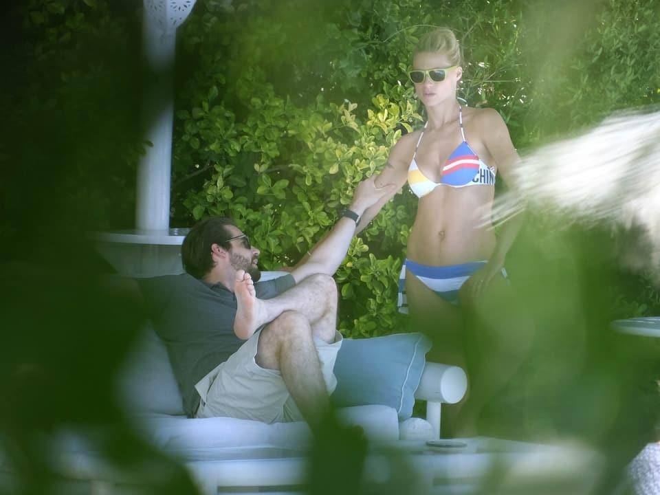 Tomaso Trussardi auf einer Liege sitzend, hält Michelle Hunziker, die einen Bikini trägt, am Arm.