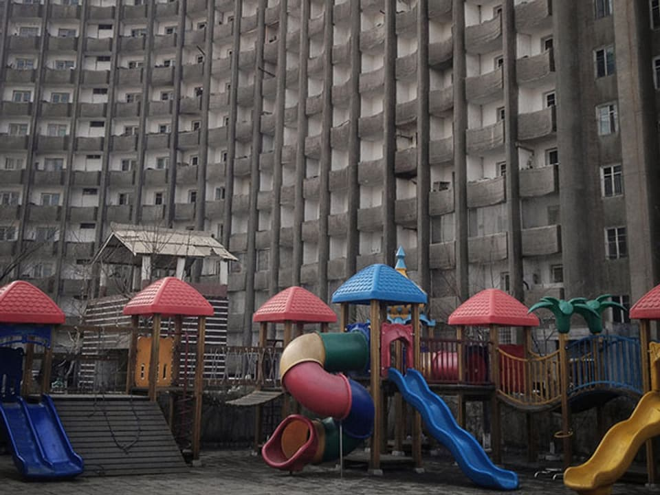 Spielplatz vor grauem Hochhaus in Pjöngjang, Nordkorea.