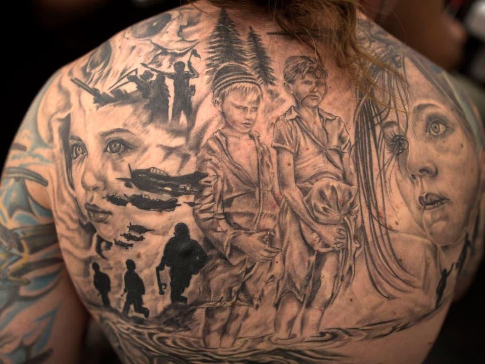 Verschiedene Gesichter auf den Rücken tätowiert.