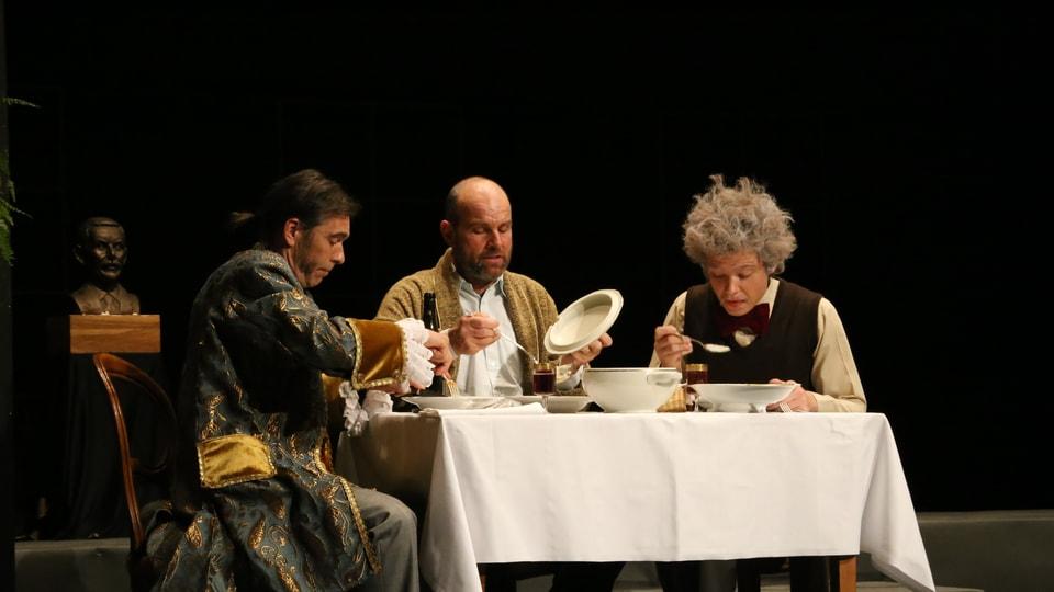 Ils 3 fisichers e pazients Newton (Beni Jehli), Möbius (Thomas Buchli) ed Einstein (Hans-Andrea Buchli) (da san.) drunat la tschaina communabla.