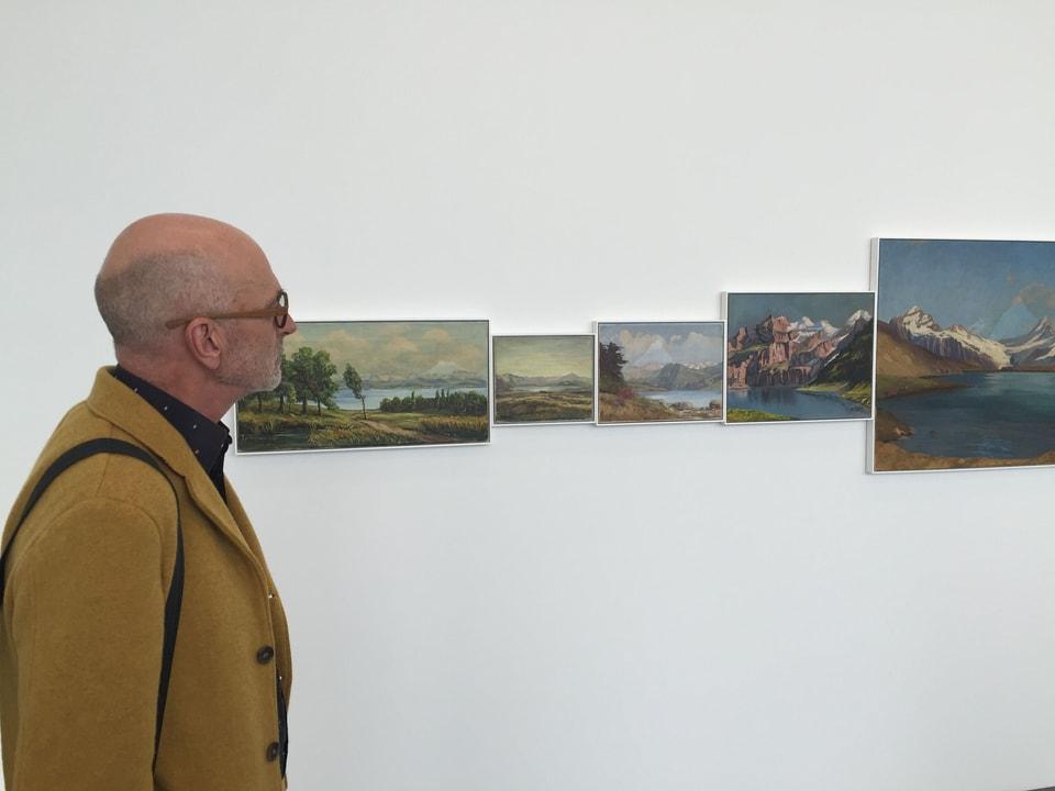 Roland Tinguely schaut sich Bilder an der Wand an.