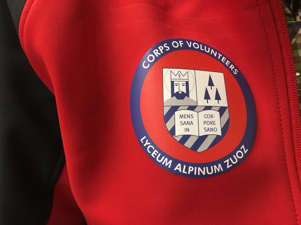 Il logo che tut ils commembers dal corp portan sin lur giaccas cotschnas.