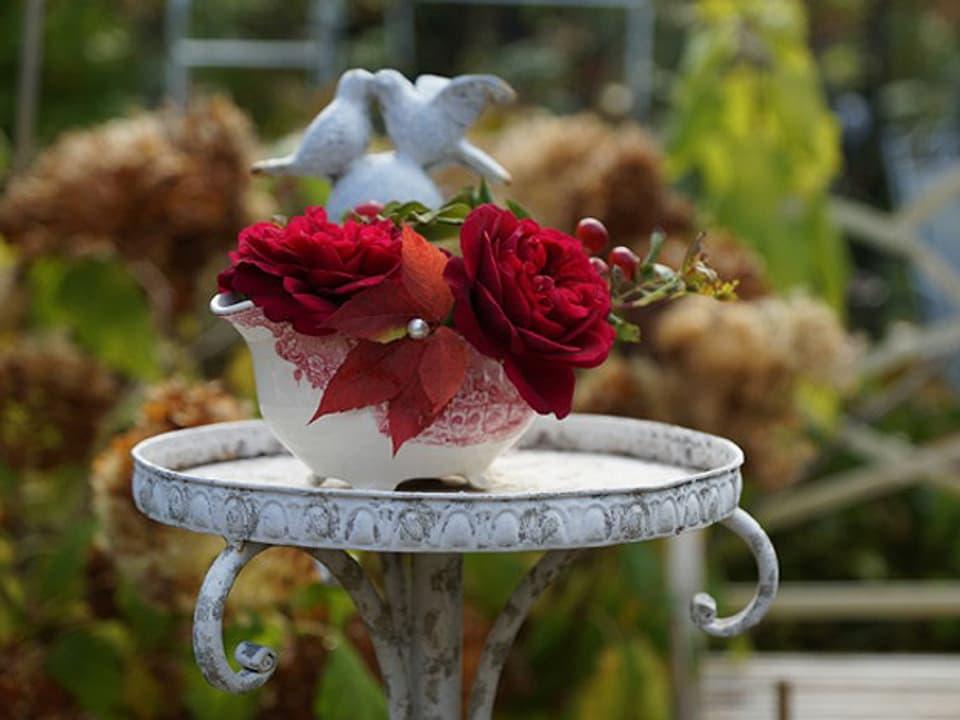 Feuerrote Rose in eine Saucière gesteckt und mit Hagebutten und einem Wildweinblatt verziert.
