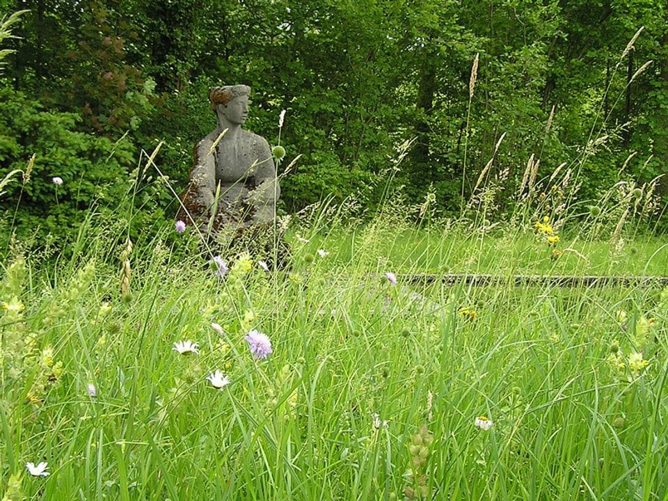 Statue am Rand des Teichs, im Vordergrund eine Blumenwiese.