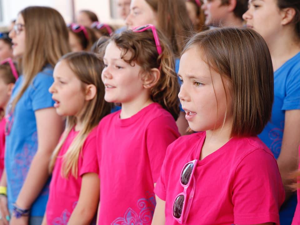 Singende Mädchen in rosaroten und hellblauen T-Shirts.