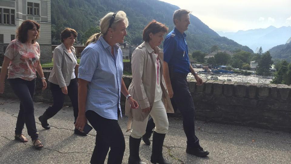 Anna Giacometti cun Barbara Janom Steiner, Doris Leuthard e Marco Steck chaminond tras la vischnanca.