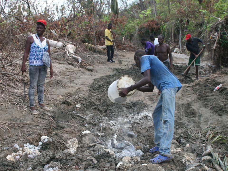 Haitianer helfen einander, eine Strasse notdürftig wieder durchgängig zu machen.