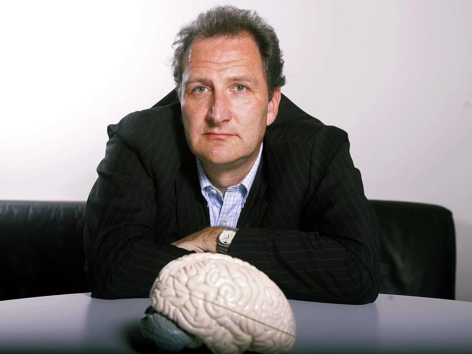Mann vor dem Modell eines Gehirns.
