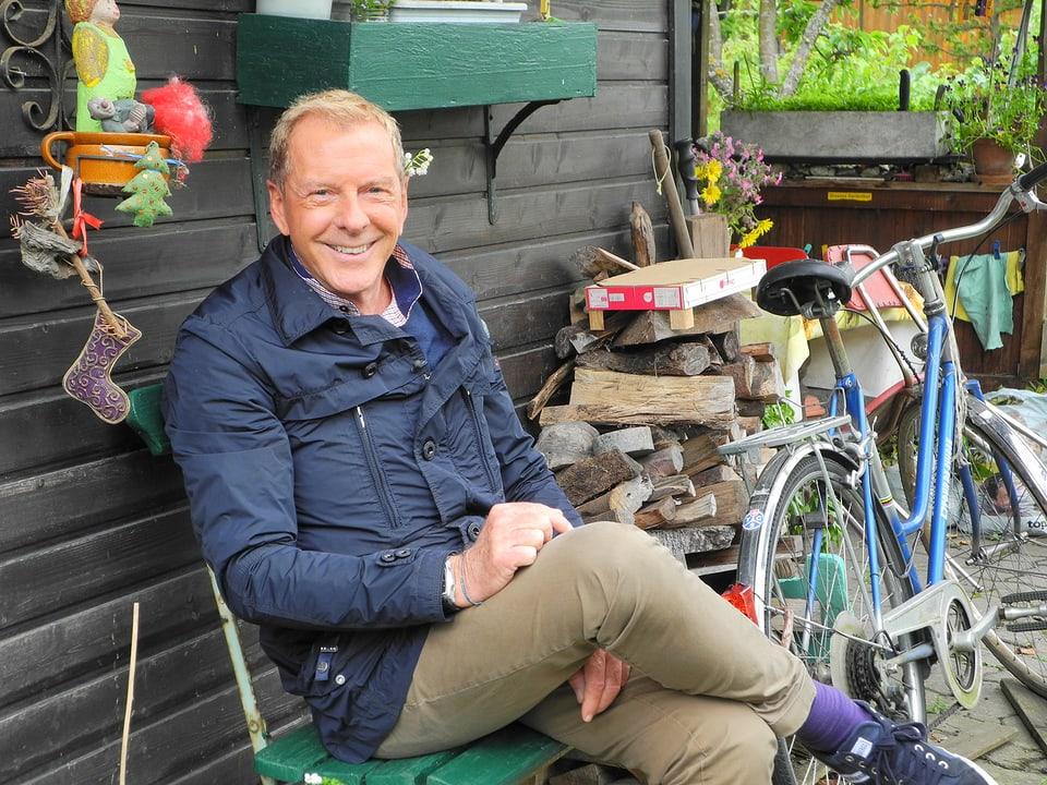 Kurt Aeschbacher sitzt auf einer grünen Gartenbank vor einer dunkel gebeizten Holzwand. Daneben ist Chemineeholz gestapelt, davor ein blaues Fahrrad. An der Wand ist Krimskrams aufgehängt, unter anderem eine Gartenfigur, ein Stoffweihnachtstannenbaum sowie ein Stoffstiefel.