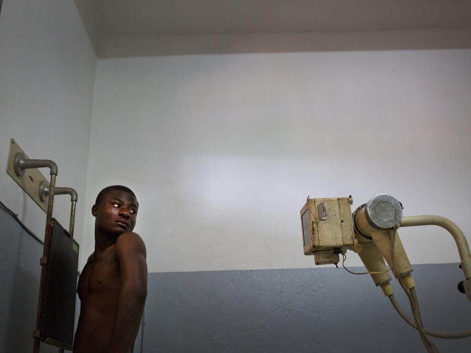 Ein Patient mustert misstrauisch das mitgenommene Röntgengerät, das hinter ihm steht.