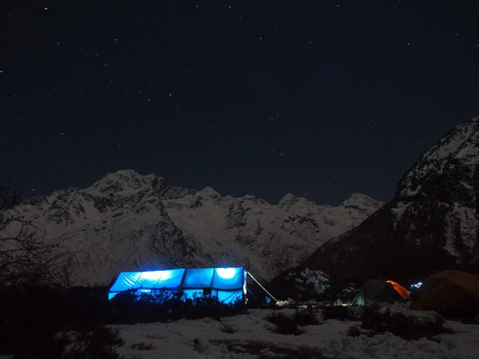 Blau erleuchtetes Zelt in der Dunkelheit.