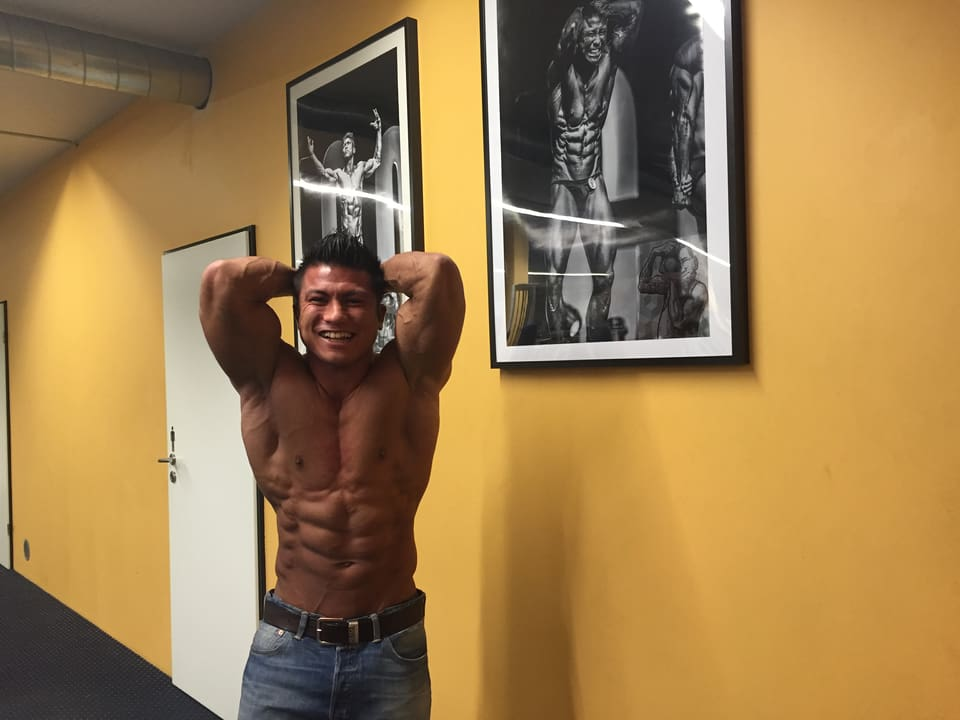 Florian Wolf posiert mit nacktem Oberkörper und zeigt sein Six-Pack.