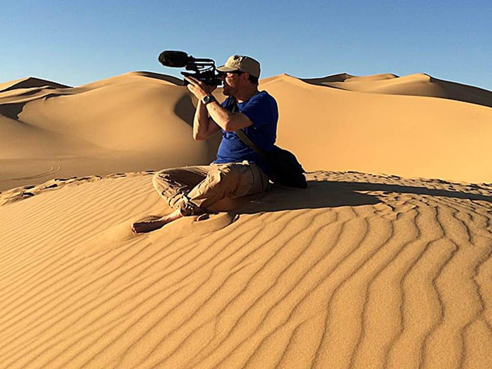Kurt Pelda mit Kamera in der Wüste.