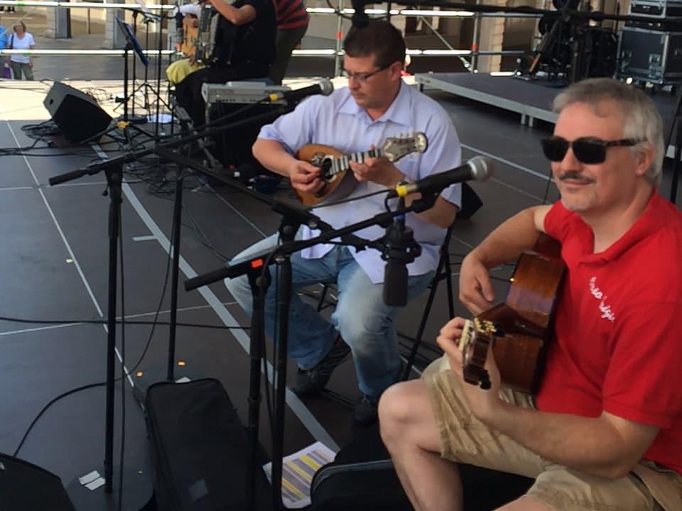 Zwe Männer spielen auf einer Konzertbühne Mandoline und Gitarre.