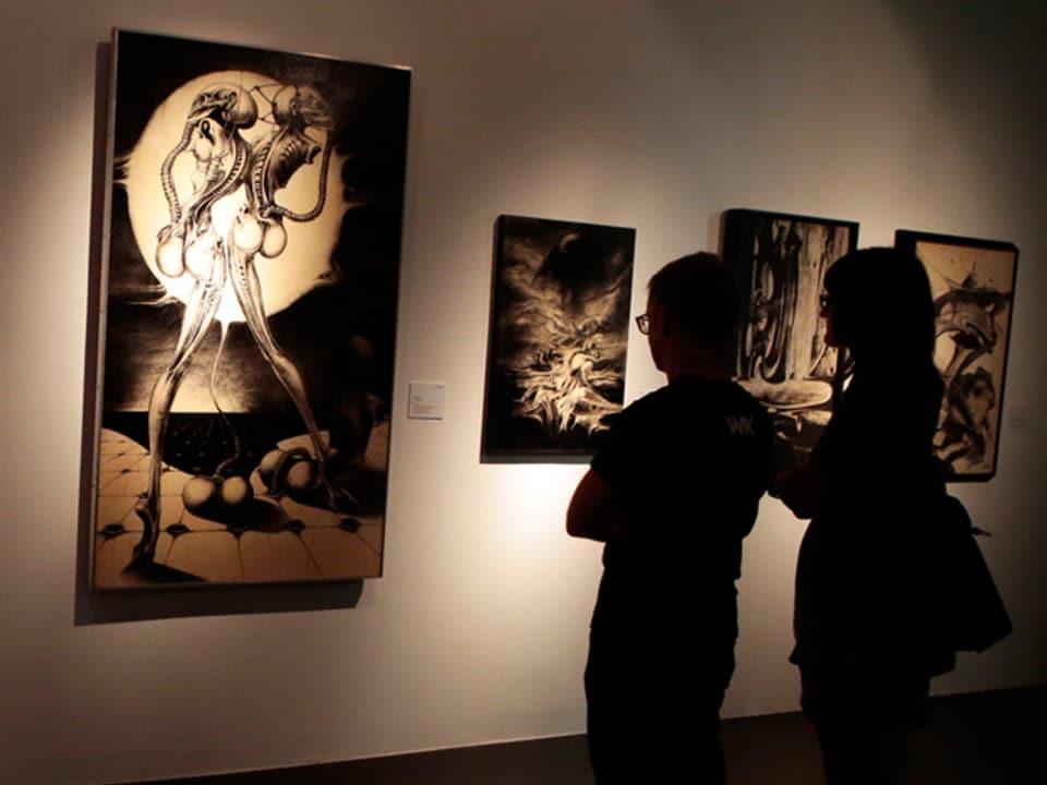 Ausstellungsbesucher betrachten ein Bild von  H.R. Giger