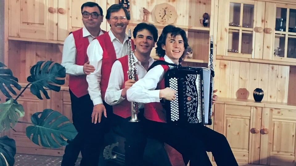 Vier Musikanten in einer Reihe stehend und sitzend in einem Wohnzimmer.