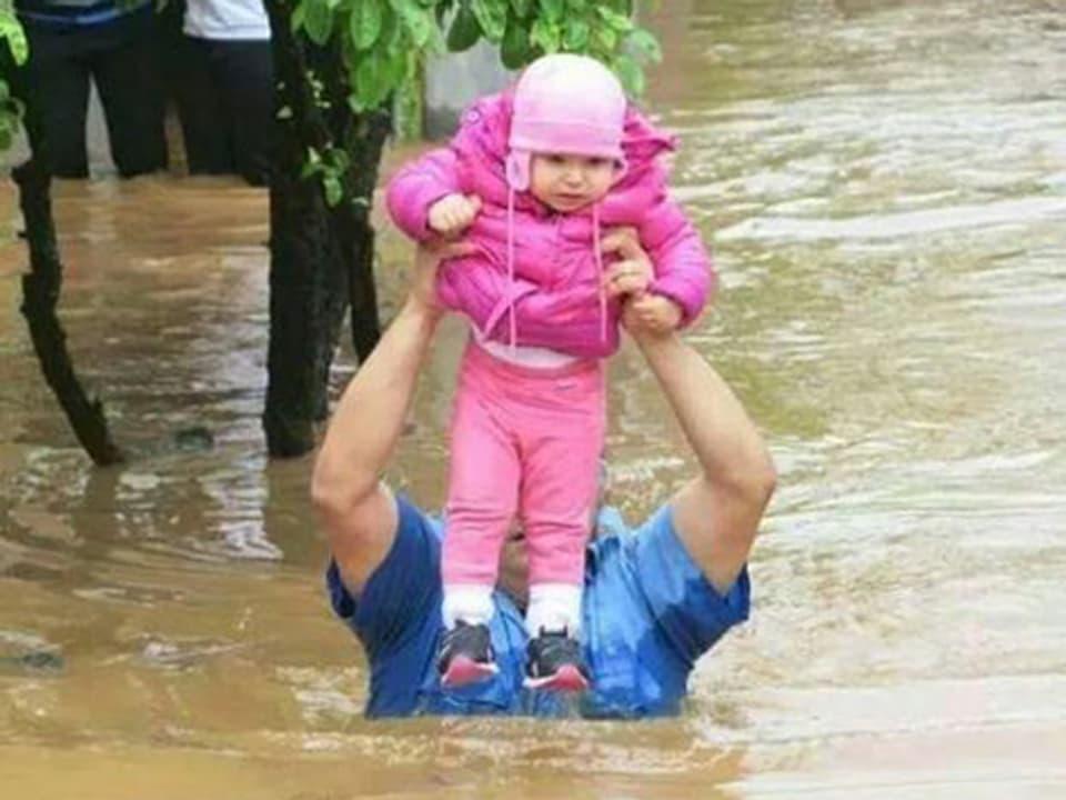 Mann watet bis zur Brust im Wasser und hält ein Kind über seinem Kopf.