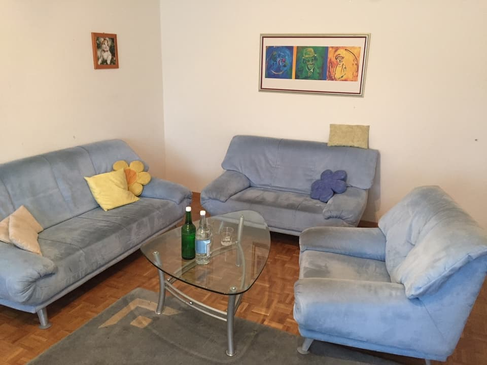 Blaues Sofa, Salontisch aus Glas, Knie-Kunst an der Wand.
