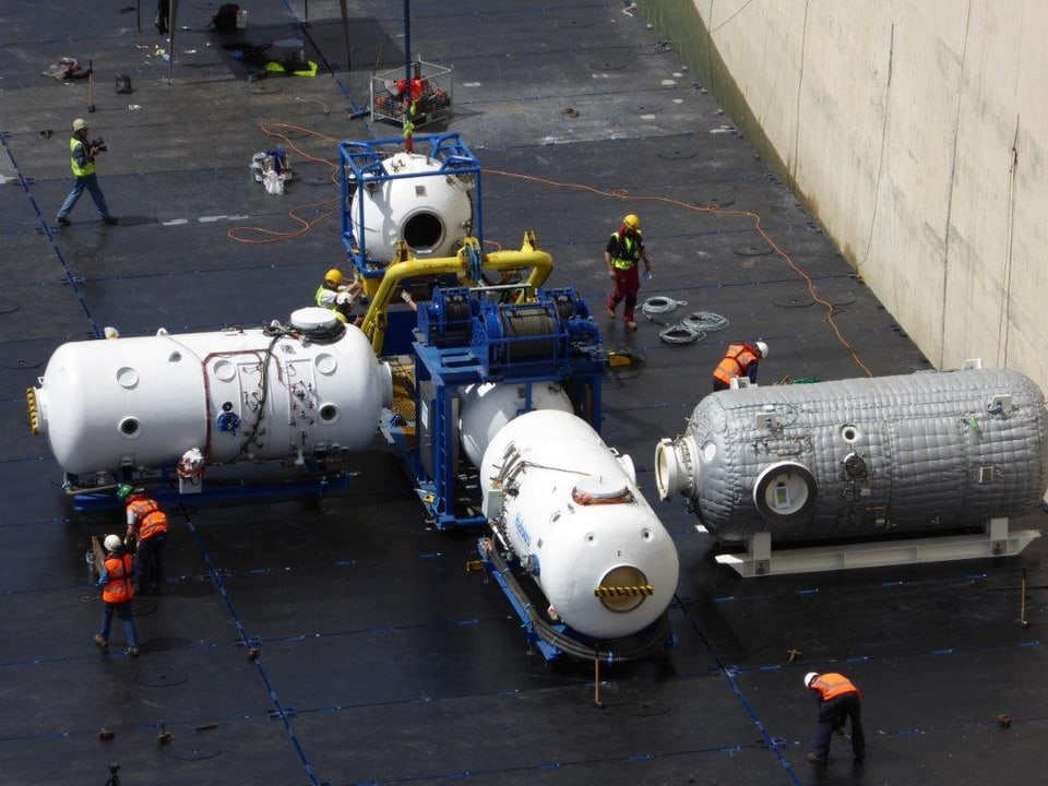 Arbeiten scharen sich um drei Druckkammern und eine Tauchglocke.