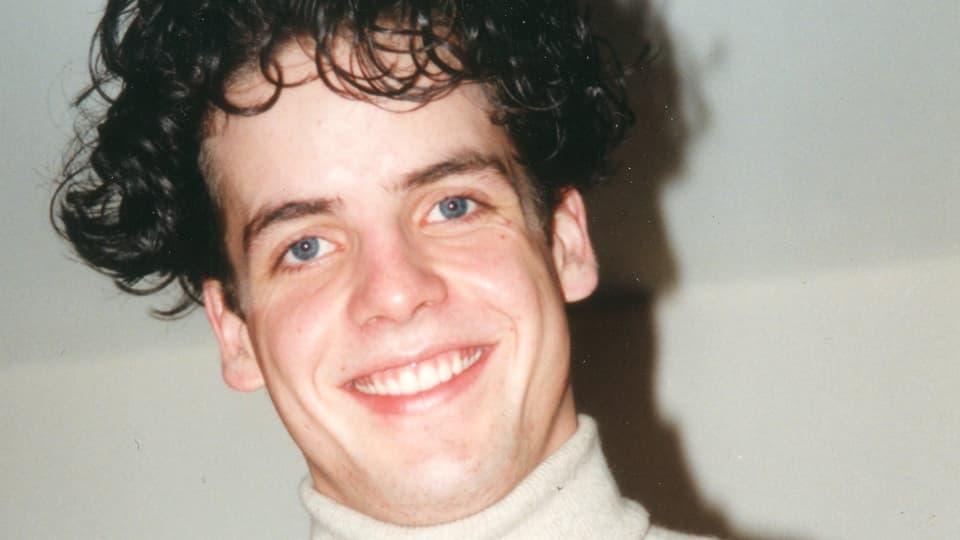 Portrait von Thomas als Lehrling mit braunen, gelockten Haaren.