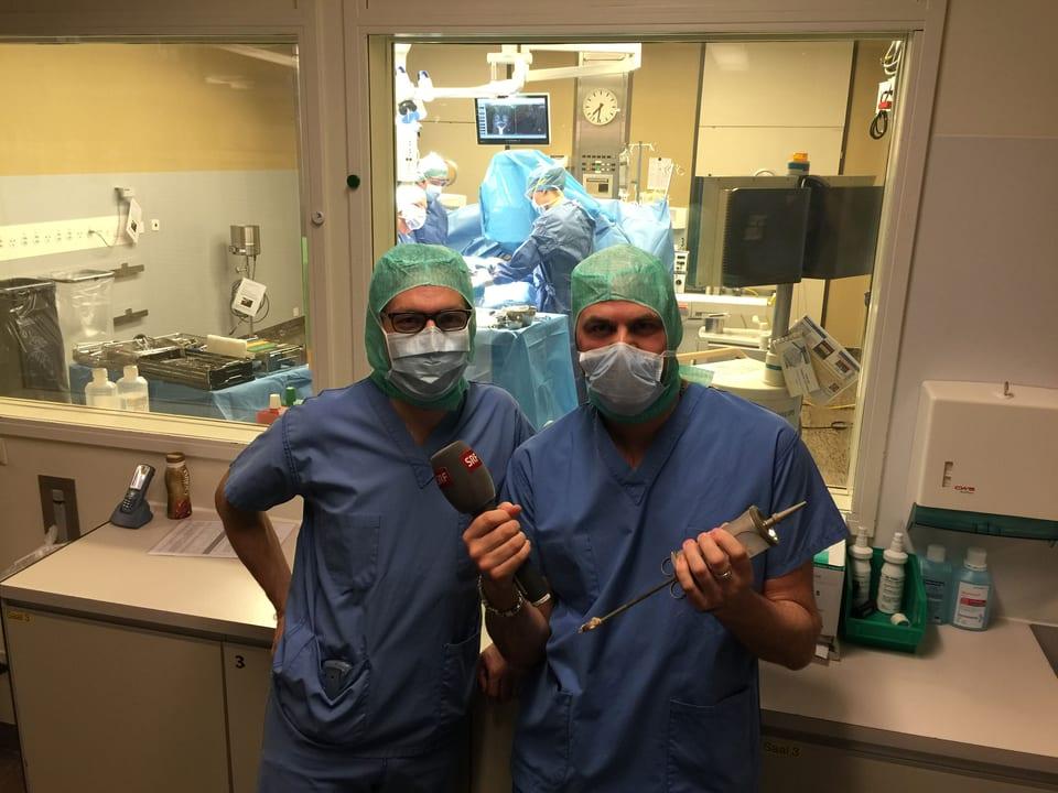 Reporter und Arzt posieren in der Operationskleidung. Reporter hält eine Spritze aus vergangener Zeit in den Händen.