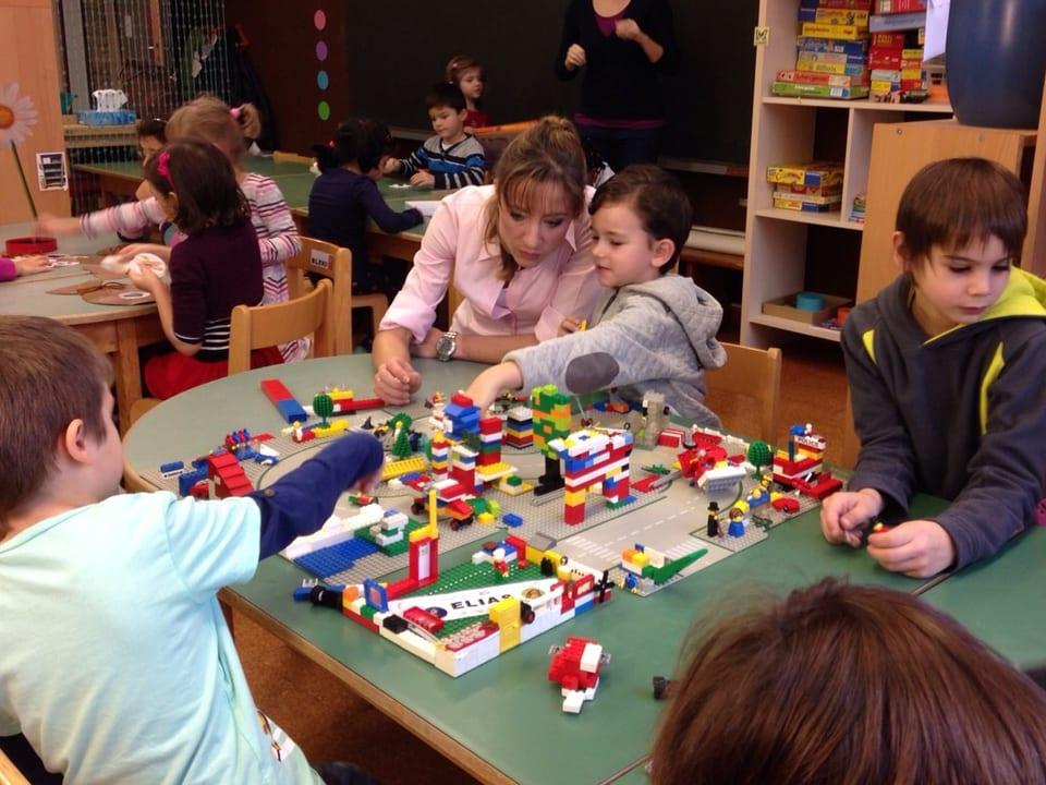 Corinne Waldmeier spielt mit einigen Jungen Lego.