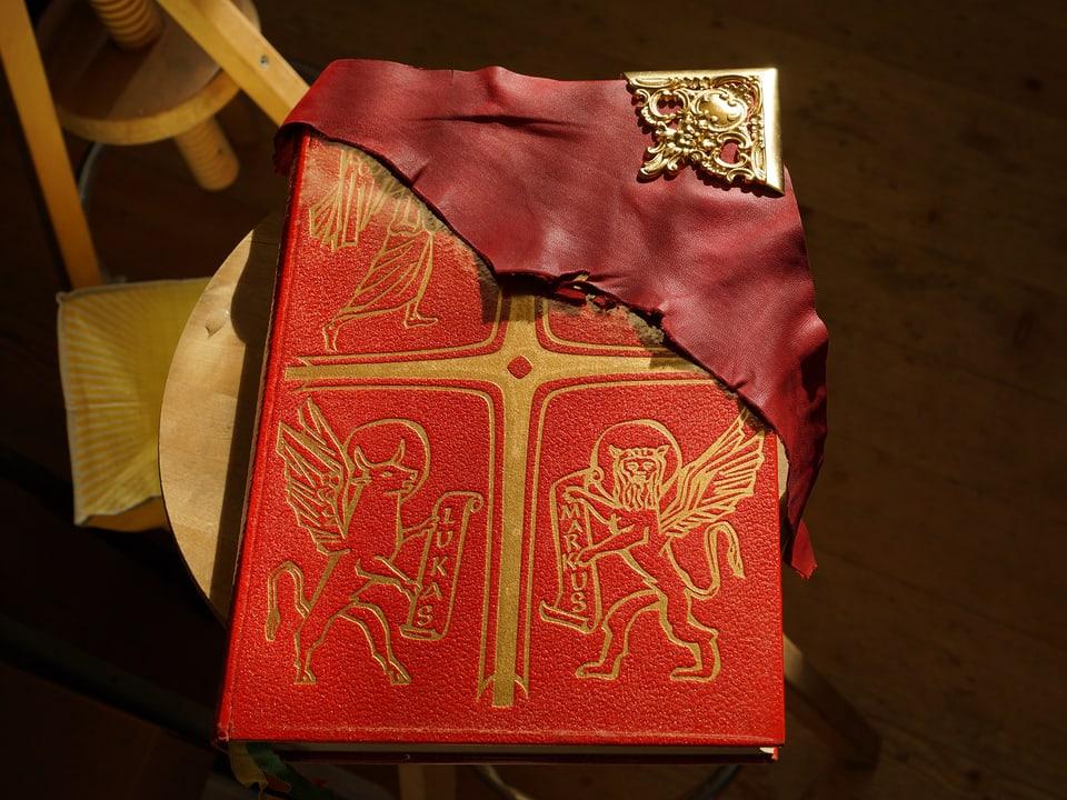 Ein Stück dunkelrotes Leder liegt auf einem Buch mit einem etwas helleren roten Einbands.