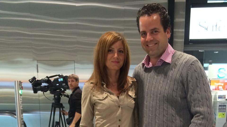 Ainara und Thomas lachen am Flughafen in die Kamera. Im Hintergrund steht Kameramann Roberto Antonilli.