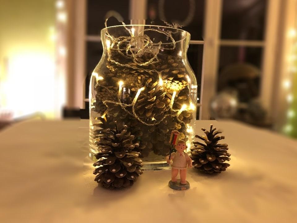 Verschidene tannenzapfen in einem grossen Glas, fast schon eine Vase. Eine Lichterkette schlängekt sich um die Zapfen.