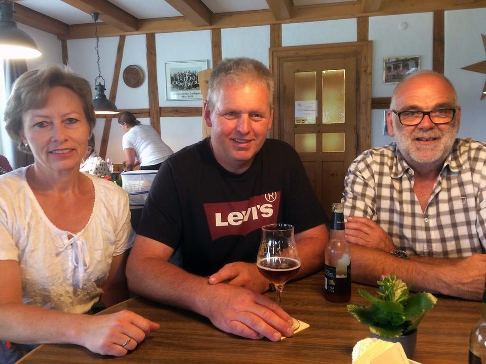 Eine Frau und zwei Männer sitzen an einem runden Tisch in einem Restaurant.