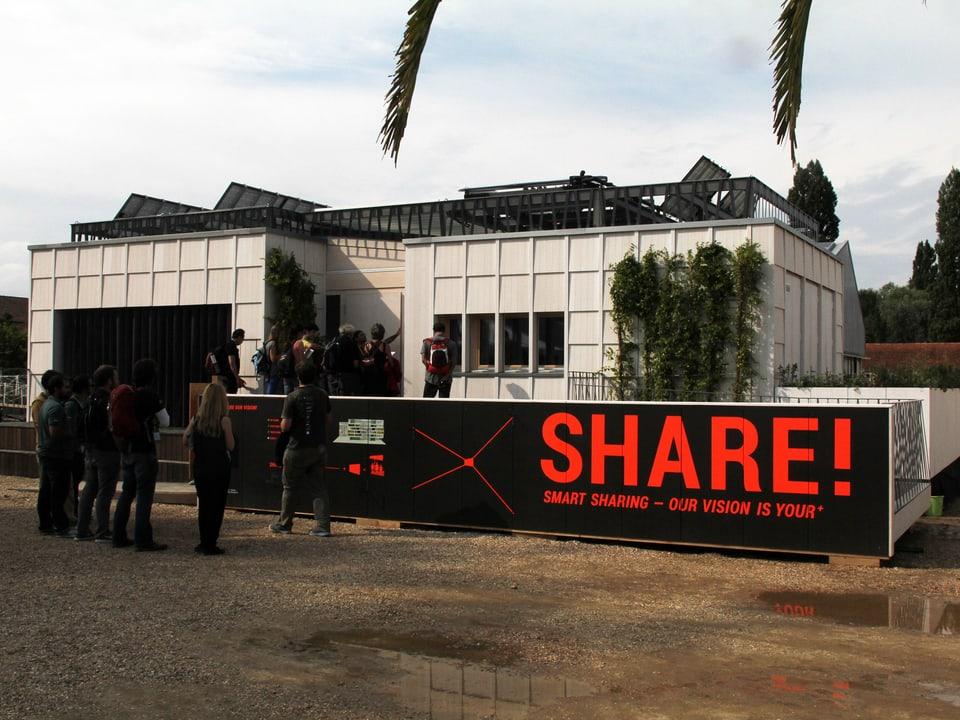 Haus-Modell mit grossem Plakat, auf dem es «SHARE!» heisst.
