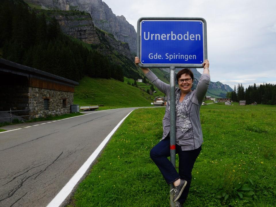 Christine Gertschen steht beim Ortsschild vom Urnerboden.