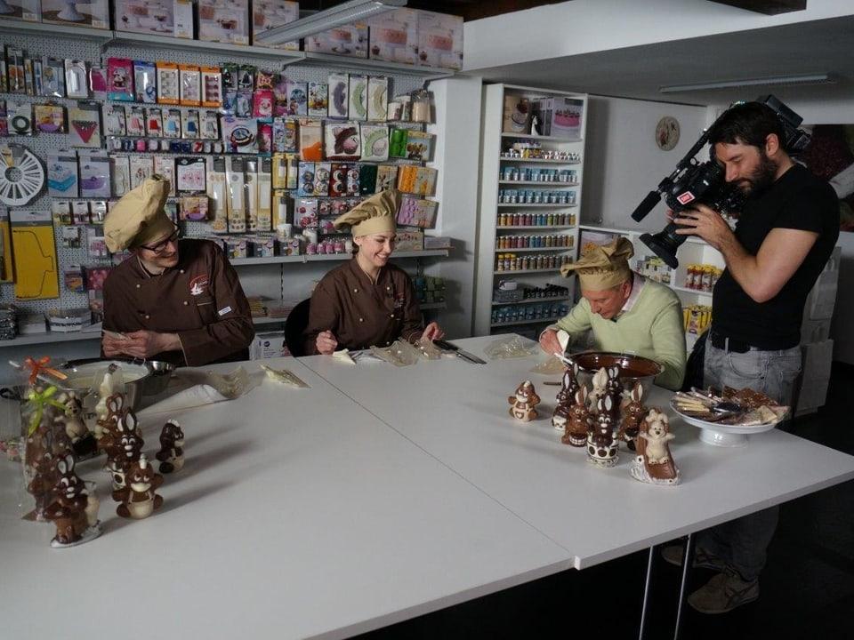 An einem grossen Tisch sitzt an der Stirnseite Kurt Aeschbacher, an der Längsseite sieht man die beiden Gründer von miniSchoggi. Kameramann filmt Kurts Osterhasenproduktion.
