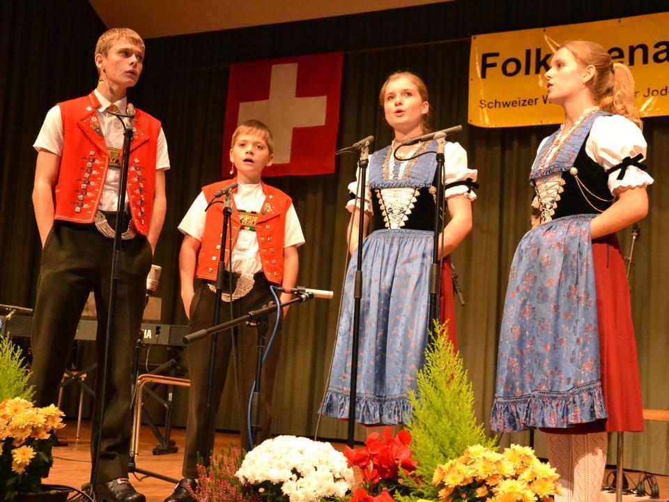 Die vier Geschwister tragen Trachten und stehen singend auf der Bühne.