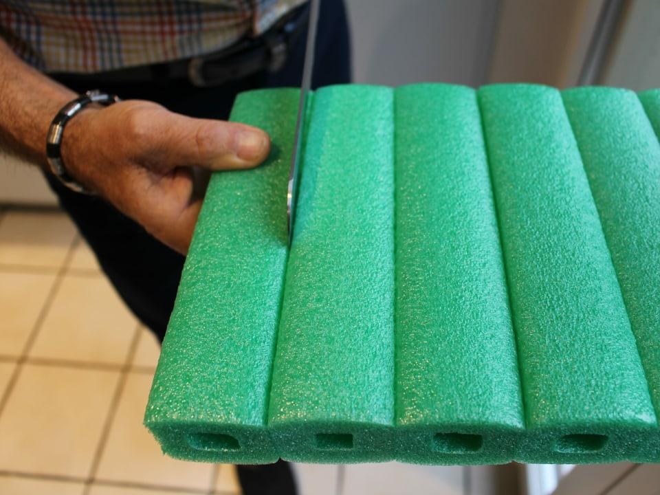 Eine Schaumstoffröhre wird mit einem Brotmesser abgeschnitten.