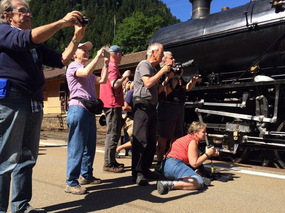 Mehrere Menschen mit Kameras fotografieren vom Perron aus die Dampflok