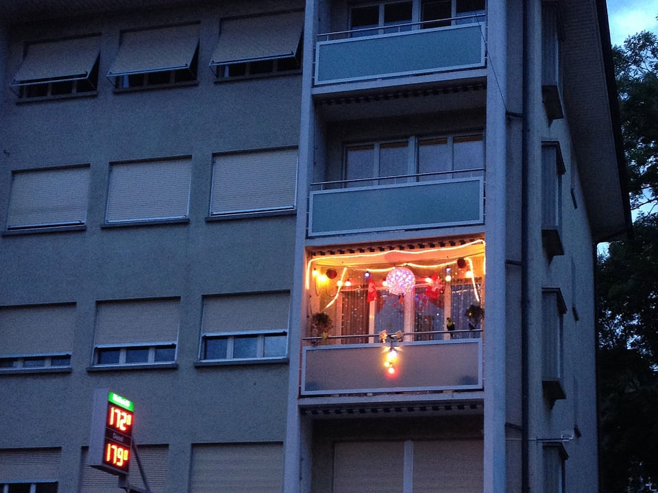 Ein hell beleuchteter Balkon in einem Wohnblock.