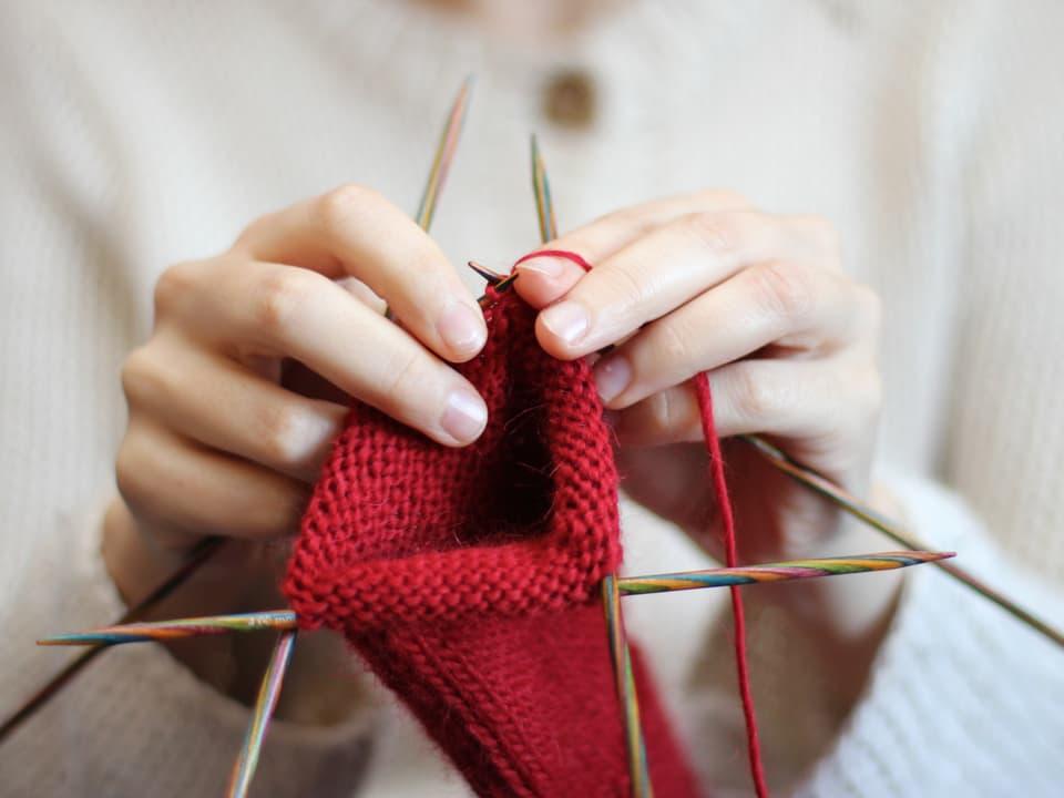Eine Frau strickt mit roter Wolle.