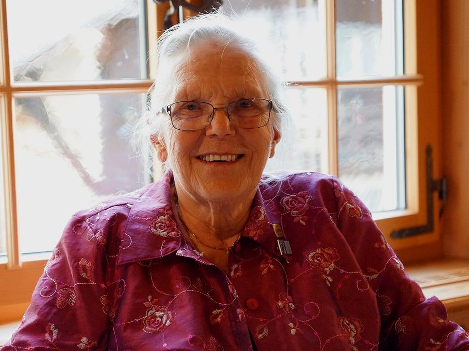 Die Seniorin mit grauen Haaren, Brille und altrosa geblümter Bluse blickt lachend in die Kamera.