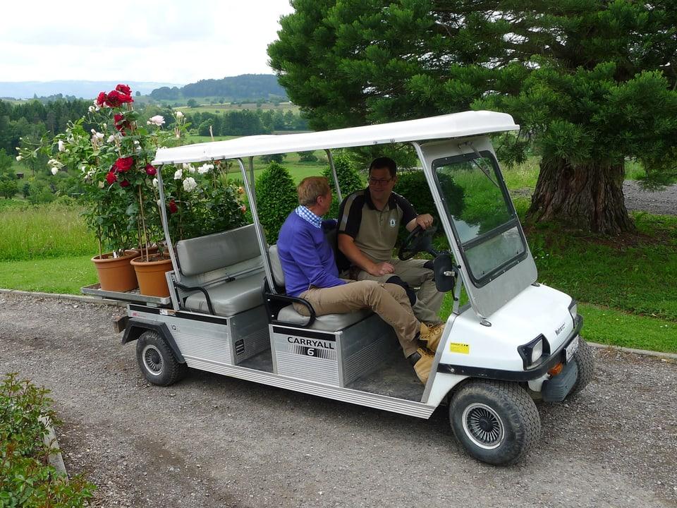 Kurt Aeschbacher und Andreas Reichenbach fahren mit einem zweckentfremdeten Golfwagen. Rote und weisse Rosenbäume sind auf der Ladefläche.