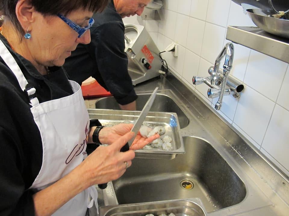 Koch und Köchin mit Kopfhörer in der Küche.