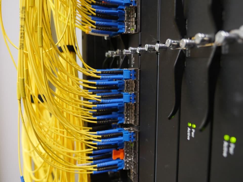 Im Router kommen Glasfaserkabel von verschiedenen Internetanbietern an: Swisscom, Sunrise, Cablecon, Google, Facebook - man weiss es genau, darf aber nichts sagen. Neutralität!