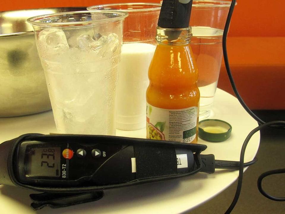 Thermometer und Getränkeflasche auf einem Tisch.