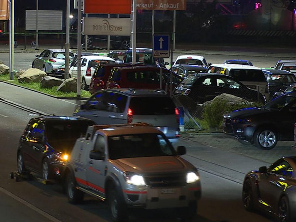 Abschleppwagen fährt mit einem blinkenden Auto auf dem Anhänger davon.