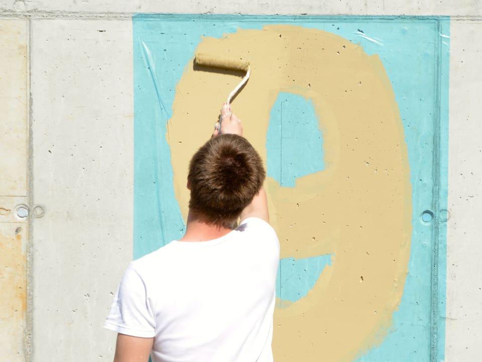 Maler malt Wand an.