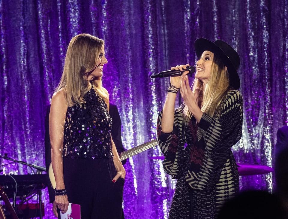 Zwei Frauen stehen mit einem breiten Lächeln auf der Bühne.