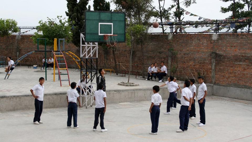 Basketball spielende Schüler im Innenhof der Schule.