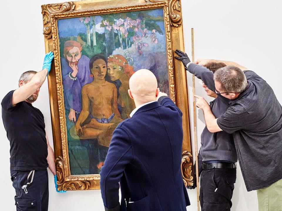 Männer hängen ein Bild von Paul Gauguin auf.